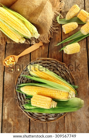 Fresh corn on cobs on wicker mat on wooden table, top view - stock photo