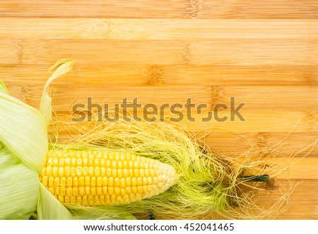 Fresh corn on cobs on wooden background, closeup - stock photo