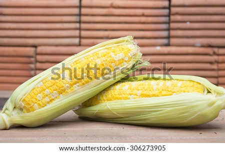Fresh corn on wooden floor with wooden background - stock photo