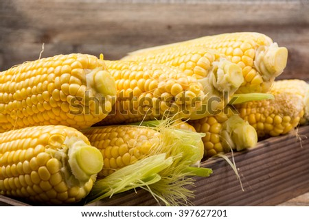 Fresh corn with leaves on wooden background - stock photo