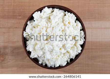 Fresh cottage cheese in a bowl on a wooden table. - stock photo