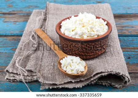 Fresh cottage cheese in a ceramic dish and spoon on painted blue wooden boards. - stock photo