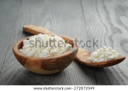fresh cottage cheese in a wood bowl on a wooden table - stock photo
