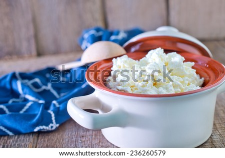 fresh cottage cheese in bowl and on a table - stock photo