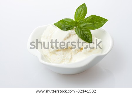 Fresh cottage cheese with basil leaves - stock photo