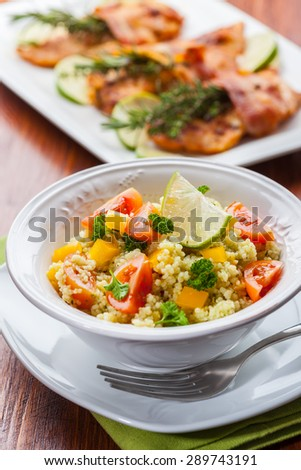 Fresh couscous salad for summer with tomato, pepper with olives - stock photo
