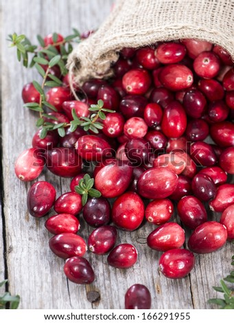 Fresh Cranberries on vintage wooden background - stock photo