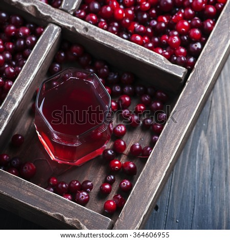 Fresh cranberry juice on the wooden table, selective focus and square image - stock photo