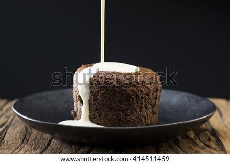 Fresh cream being poured over a Chocolate Lava Cake. Chocolate pudding sitting on a rustic wooden table. - stock photo