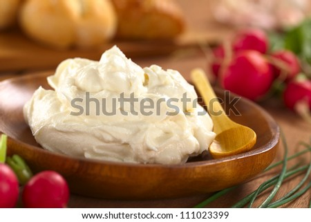 Fresh cream cheese spread on wooden plate with radish and chives (Selective Focus, Focus one third into the cream cheese) - stock photo