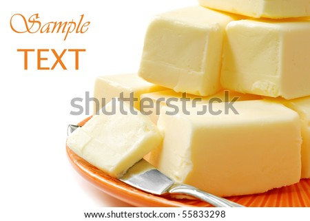 Fresh creamy real butter on plate with knife on white background with copy space. - stock photo