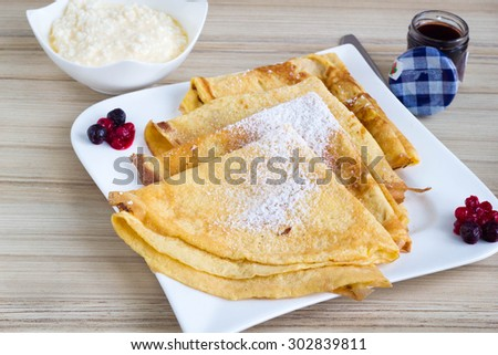 Fresh crepes with jam and cream on a wooden table. - stock photo