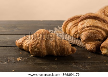 Fresh croissant on rustic table