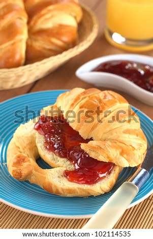 Fresh croissant with butter and strawberry jam, bread basket and orange juice in the back (Selective Focus, Focus on the front of the strawberry jam) - stock photo