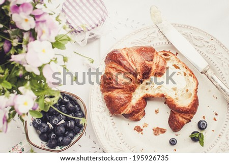 Fresh croissant with butter. Blueberries and flowers on table. Selective focus, top view - stock photo