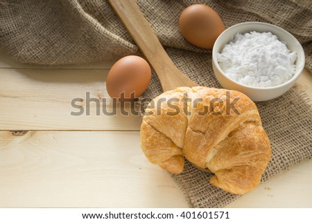 fresh croissant with flour and egg. selective focus.