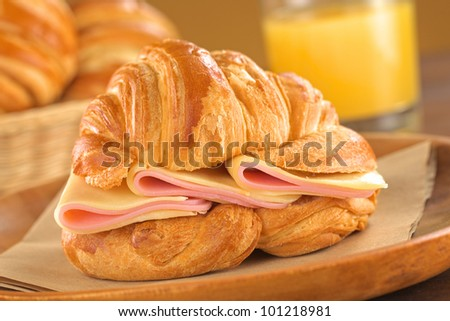 Fresh croissant with ham and cheese on rustic wooden plate with bread basket and orange juice in the back (Selective Focus, Focus on the ham and cheese slices) - stock photo