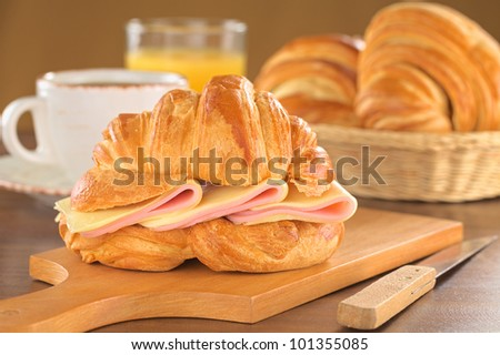 Fresh croissant with ham and cheese on wooden board with coffee, orange juice and bread basket in the back (Selective Focus, Focus on the front of the croissant and the ham and cheese slices) - stock photo