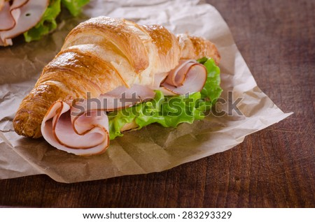 Fresh croissant with ham and salad leaf on dark wooden background - stock photo