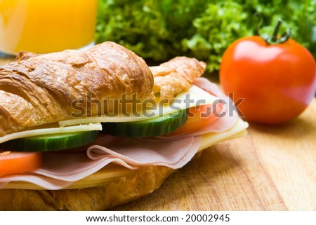 Fresh croissant with ham, cheese and salad on a wooden board - stock photo