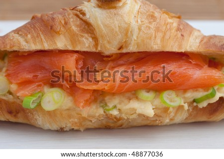 Fresh croissant with smoked salmon, scrambled eggs and garnished with spring onion