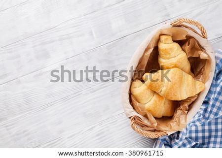 Fresh croissants basket on wooden table. Top view with copy space