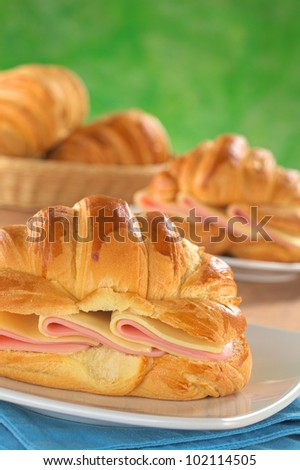 Fresh croissants with ham and cheese on plate with bread basket in the back (Selective Focus, Focus on the front of the croissant and the ham and cheese slices) - stock photo
