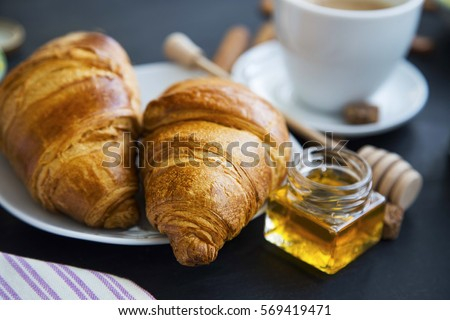 Fresh croissants with honey jar and coffee, breakfast setting, selective focus