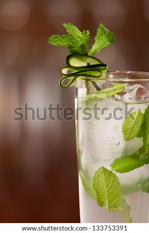 fresh cucumber mojito cocktail served on a bar garnished with a cucumber slice and mint - stock photo