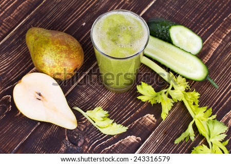 Fresh cucumber, pear and celery juice. Slices of fruits and vegetables on wooden background - stock photo