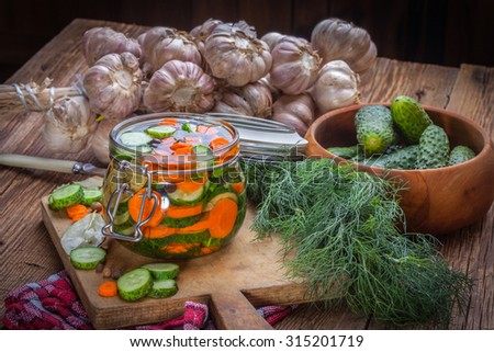 Fresh cucumbers and carrot in the jar on wooden table. - stock photo