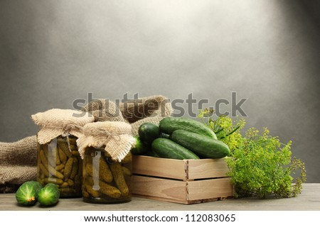 fresh cucumbers in wooden box, pickles and dill, on grey background - stock photo