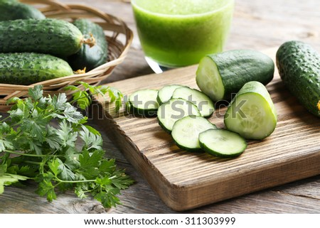 Fresh cucumbers on cutting board on grey wooden background - stock photo