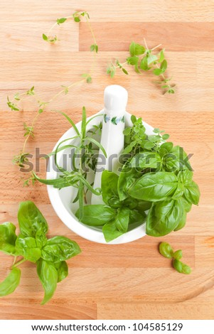 Fresh culinary aromatic herbs basil, thyme and rosemary in mortar with pestle on wooden background. Top view. - stock photo