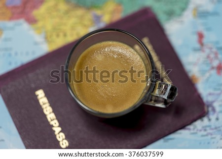 Fresh cup of coffee and passport on a world map viewed from above in a concept of travel, tourism and vacations - stock photo