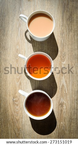 Fresh cups of tea and coffee with shadows of cups on a wooden table