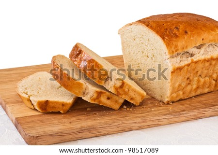 fresh cut into slices of bread with crispy crust, on a wooden board - stock photo