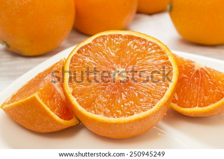 """fresh cut orange on a plate with whole oranges in background on a white tablecloth""""fresh cut orange"""" - stock photo"""