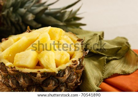 Fresh cut pineapple served in a natural bowl, set against colorful napkins on a beige linen tablecloth. - stock photo