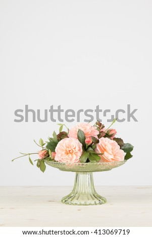 Fresh cut pink garden roses arranged in a green glass pedestal vase, in vertical format with copy space. - stock photo