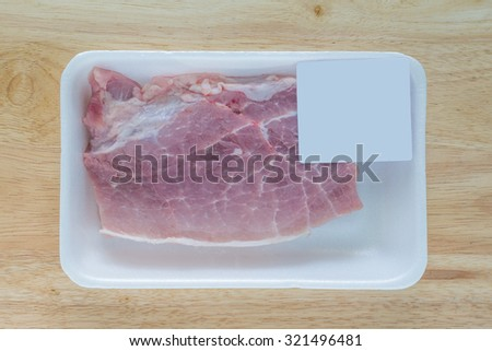 Fresh cut pork shoulder steak wrapped in a white foam butcher tray with white label attached on plastic wrap, on wood table