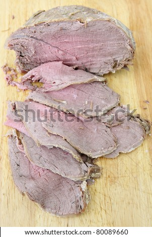 Fresh cut slices of cold boiled topside of beef with the joint on a wooden chopping boards