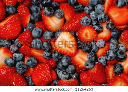 fresh cut strawberries and blueberries piled up high - stock photo