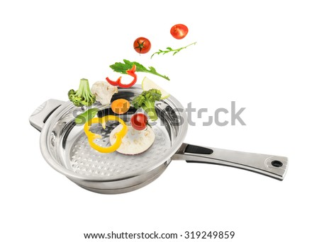 Fresh cut vegetables falling in the metal frying pan isolated on white background