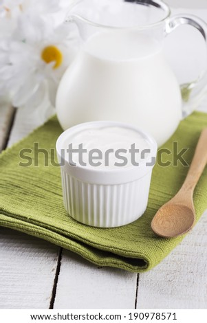 Fresh dairy products - sour cream, milk on wooden table.  Rustic style. Selective focus,vertical. Bio/organic/natural ingredients. Healthy eating. - stock photo