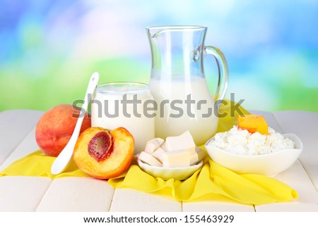 Fresh dairy products with peaches on wooden table on natural background - stock photo