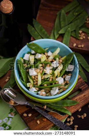 Fresh delicious cucumber, pods green peas, feta and pine nuts salad, dark style photo - stock photo