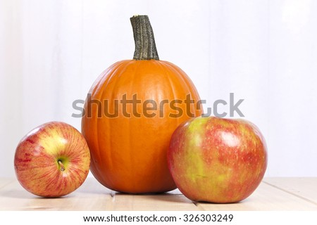 Fresh delicious fall harvest of orange pumpkin and sweet apples on light wooden table for Thanksgiving holiday. - stock photo