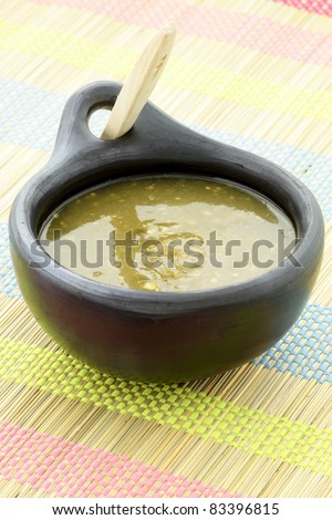 fresh delicious,flavorful tomatillo sauce in colombian clay dish - stock photo