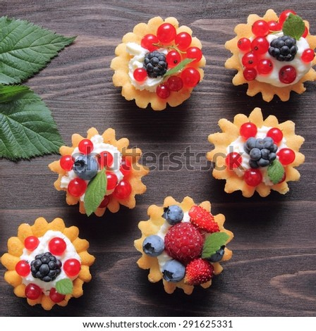 Fresh delicious fruit tarts with cream and berries - stock photo